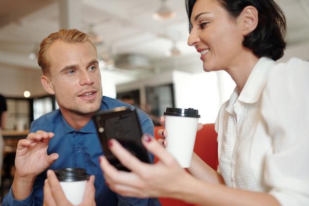 Excité beau jeune homme d'affaires partageant son idée créative avec un collègue quand ils boivent du café au café