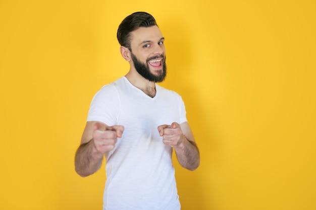 Excité beau jeune homme barbu dans un t-shirt blanc pointe vers l'avant