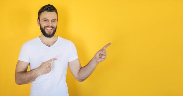 Excité beau jeune homme barbu dans un t-shirt blanc pointe vers l'extérieur