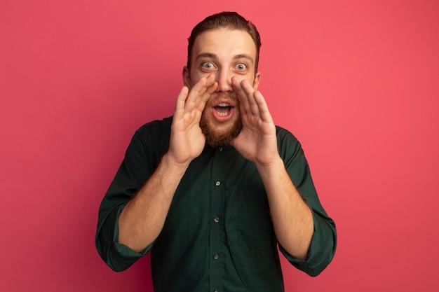 Excité bel homme blond tient les mains près de la bouche isolée sur le mur rose