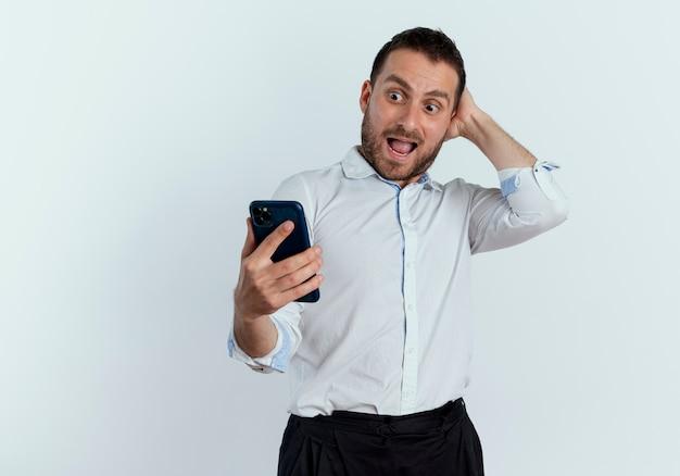 Excité bel homme met la main sur la tête derrière en regardant téléphone isolé sur mur blanc