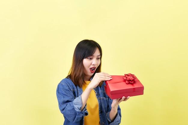 Excité belle femme asiatique tenant une boîte-cadeau rouge