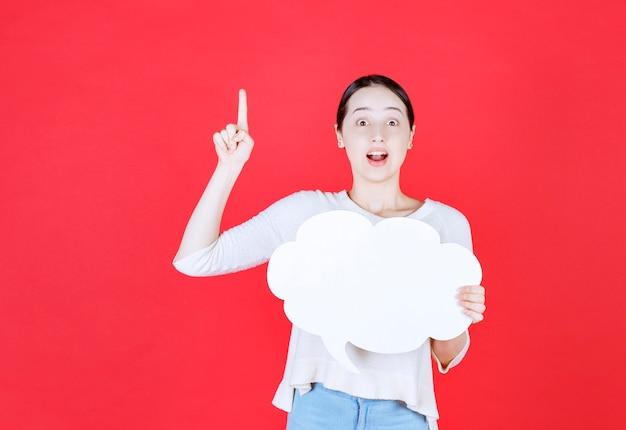 Excité belle femme tenant une bulle de dialogue avec une forme de nuage