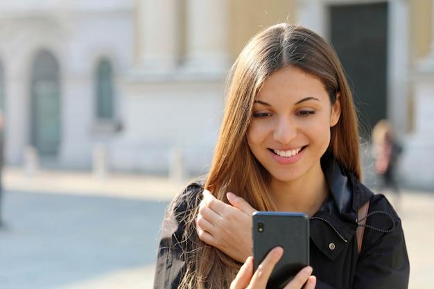 Excité belle jeune femme lisant de bonnes nouvelles sur un téléphone intelligent à l'extérieur
