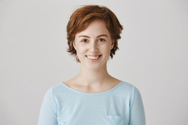 Excité belle jeune femme souriant d'espoir à la caméra