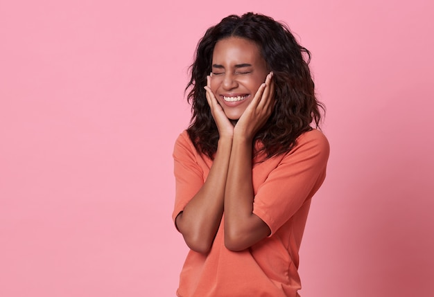 Excité le bonheur de belle femme africaine portant un t-shirt orange décontracté sur rose.