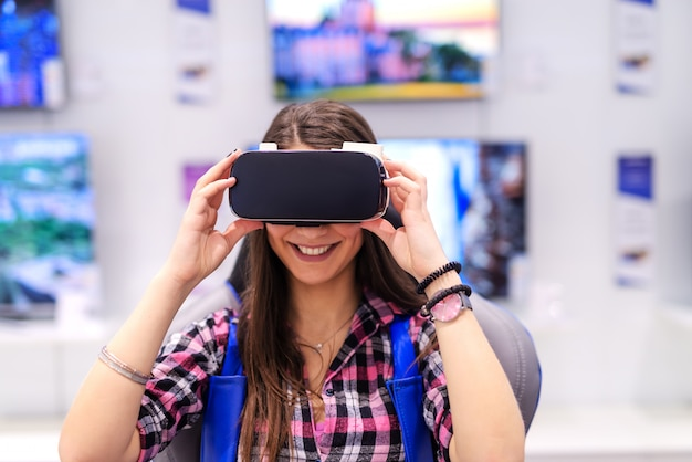 Excité brune caucasienne souriante aux cheveux longs ayant essayé la réalité virtuelle