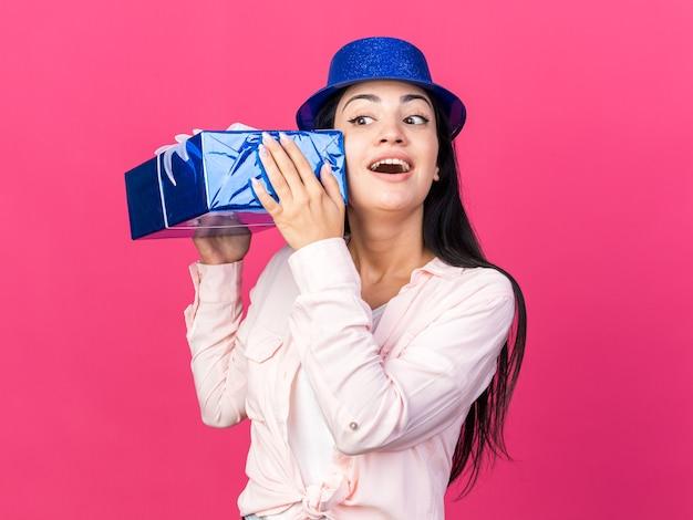 Excité à côté belle jeune femme portant un chapeau de fête tenant une boîte-cadeau