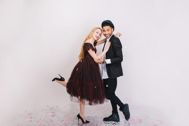 Excité couple amoureux s'amuser. vêtements de soirée de luxe, exprimant la positivité, souriant, dansant, riant.