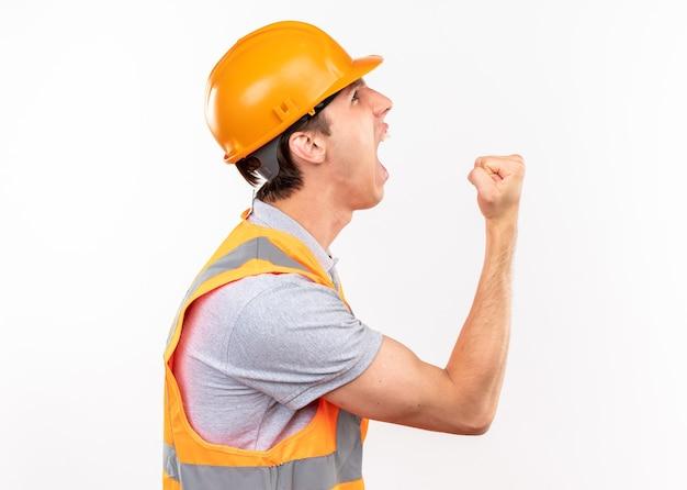 Excité debout en vue de profil jeune homme constructeur en uniforme montrant un geste oui