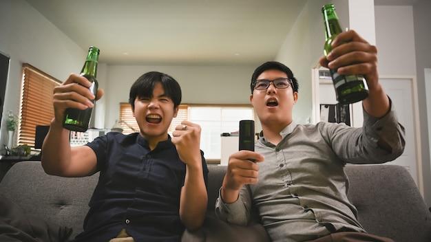 Excité deux hommes buvant de la bière acclamant le football sur un canapé à la maison.
