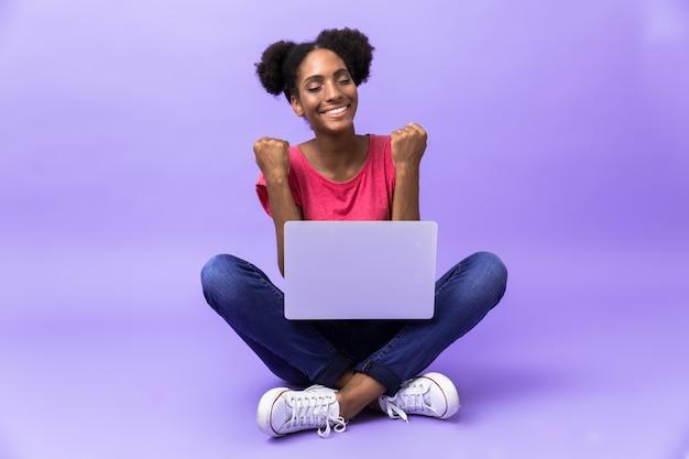 Excité, femme américaine africaine, sourire, et, utilisation, argent, ordinateur portable, quoique, reposer plancher, à, jambes croisées, isolé