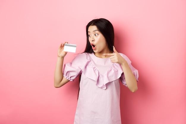 Excité femme asiatique pointant et montrant une carte de crédit en plastique, haletant étonné, concept de shopping.