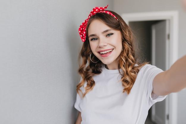 Excité femme blanche en boucles d'oreilles faisant selfie le matin. photo intérieure d'une femme élégante et heureuse porte un ruban dans les cheveux.