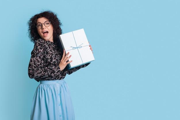 Excité femme caucasienne tient un cadeau sur un mur de studio bleu avec espace libre portant une robe et des lunettes