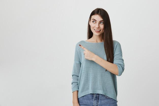 Excité femme intriguée souriant, doigt pointé vers la gauche