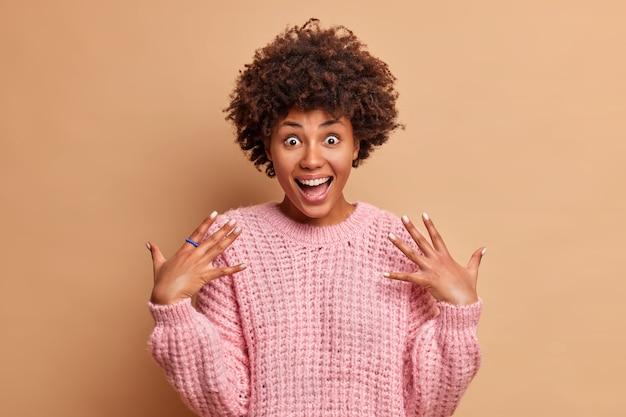 Excité femme joyeuse lève les paumes et sourit largement a surpris l'expression du visage porte un pull tricoté occasionnel exprime des émotions positives pose contre le mur brun du studio