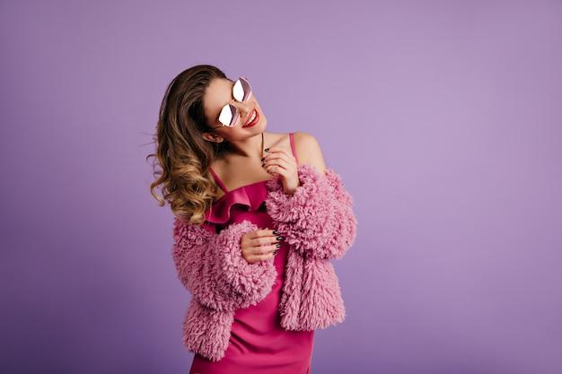 Excité femme posant en veste moelleuse à la mode