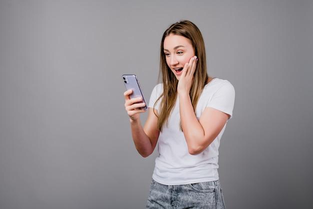 Excité femme regardant écran de téléphone isolé sur gris