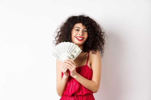 Excité femme en robe rouge gagner de l'argent, montrant des billets d'un dollar et souriant heureux, debout sur fond blanc.