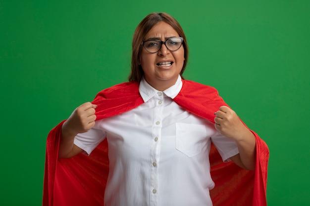 Excité femme de super-héros d'âge moyen portant des lunettes montrant oui geste isolé sur vert