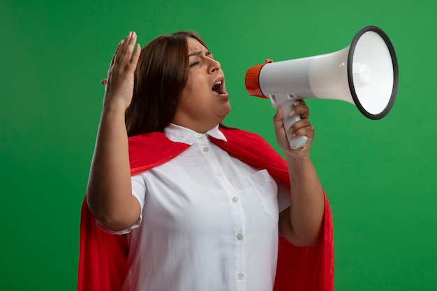 Excité femme de super-héros d'âge moyen à la recherche de côté parle sur haut-parleur isolé sur fond vert