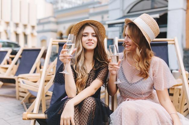 Excité fille blonde en robe blanche transparente regardant soeur qui pose tenant un verre à vin