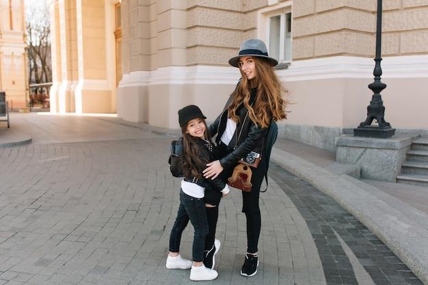 Excité fille brune au chapeau et veste élégante embrassant la jambe de sa mère debout au milieu de la rue.