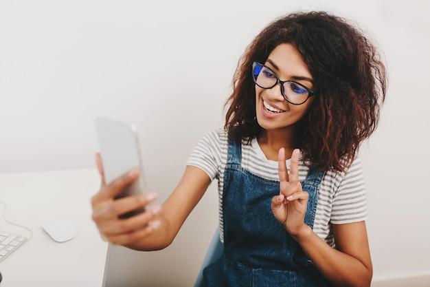 Excité fille noire avec une jolie coiffure prenant une photo d'elle-même au repos du travail