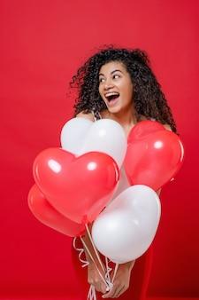 Excité fille noire ludique avec des ballons d'hélium isolé sur rouge