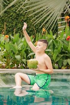 Excité garçon préadolescent assis dans la piscine avec un cocktail de noix de coco et en agitant la main pour attirer l'attention d'un ami