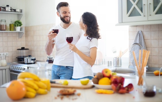 Excité heureux beau jeune couple amoureux cuisiner dans la cuisine et s'amuser ensemble tout en faisant une salade de fruits frais et sains
