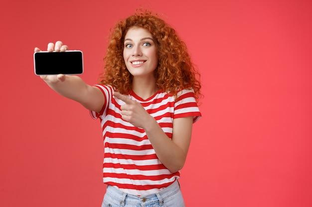 Excité heureux beau rousse frisée show horizontal smartphone écran pointant gadget d'affichage souriant heureux fier battement amis score jeu debout fond rouge. notion de technologie