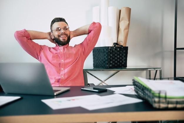 Excité heureux bel homme barbu dans des vêtements décontractés sourit et crie en raison de gagner dans un travail, un pari ou une loterie
