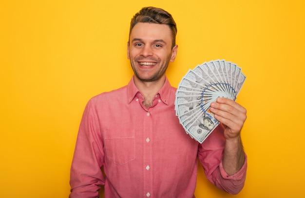 Excité heureux bel homme réussi dans des vêtements décontractés pose avec de l'argent dans les mains alors qu'il isolé sur fond jaune