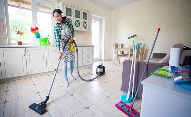 Excité et heureux belle jeune femme dans un tablier nettoie le sol dans sa cuisine à la maison et danse