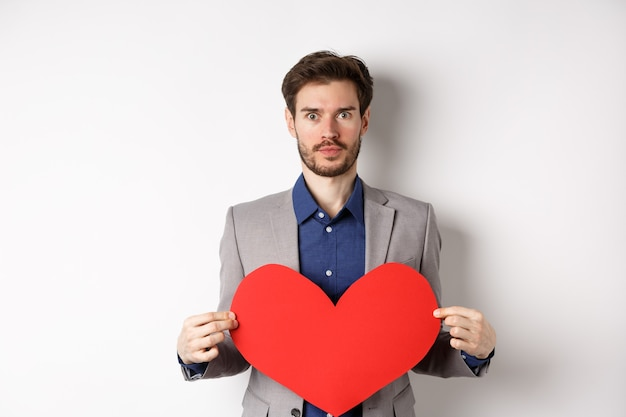 Excité homme caucasien en costume regardant la caméra, tenant la découpe de gros coeur rouge le jour de la saint-valentin, debout sur fond blanc. copier l'espace