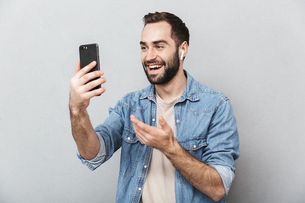Excité homme gai portant chemise isolé sur mur gris, portant des écouteurs, à l'aide de téléphone mobile, chat