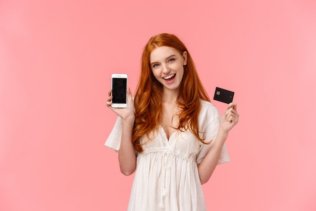 Excité, impertinent, insouciante femme aux cheveux bouclés rouges comme gaspiller de l'argent dans la boutique internet