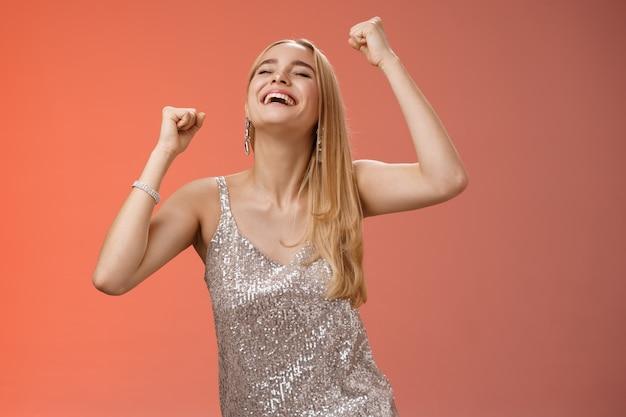Excité insouciant heureux élégant femme européenne blonde s'amusant à danser souriant largement rire bonheur appréciant la musique géniale fête à bascule éclairage piste de danse debout fond rouge.