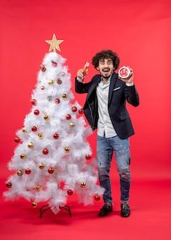 Excité jeune adulte tenant horloge et un verre de vin et debout près de l'arbre de noël sur l'image rouge