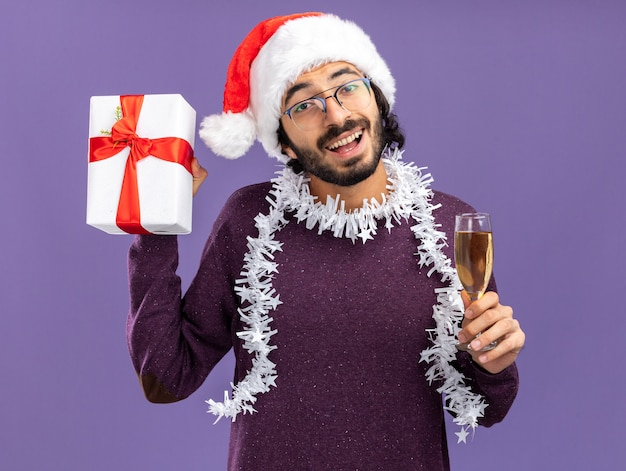 Excité jeune beau mec portant un chapeau de noël avec guirlande sur le cou tenant une boîte-cadeau avec verre de champagne isolé sur fond bleu