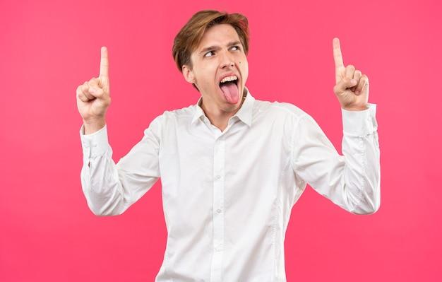 Excité jeune beau mec vêtu d'une chemise blanche montrant des points de langue vers le haut isolé sur un mur rose