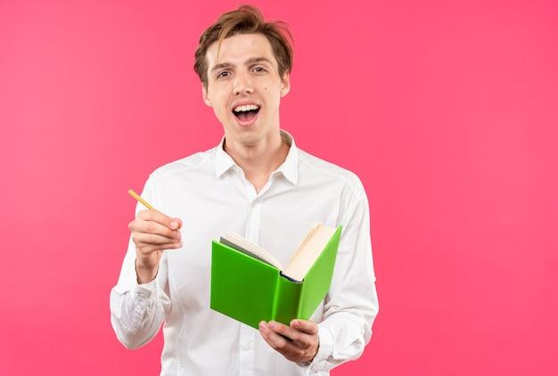 Excité jeune beau mec vêtu d'une chemise blanche tenant un livre avec un stylo