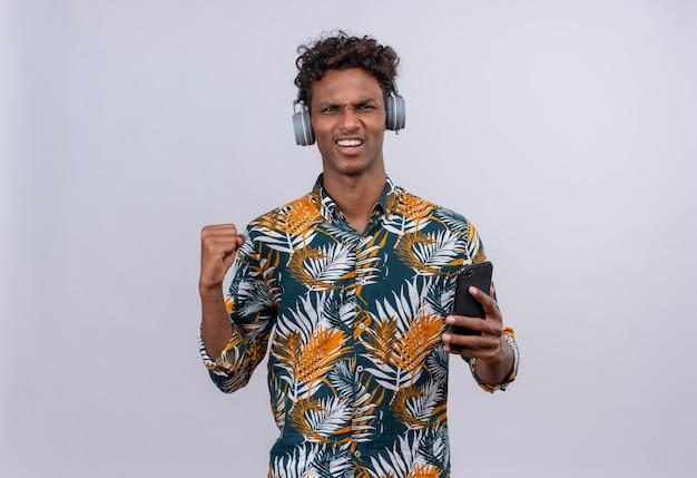 Excité jeune bel homme à la peau sombre avec des cheveux bouclés en chemise imprimée de feuilles dans les écouteurs tenant le smartphone avec le poing serré