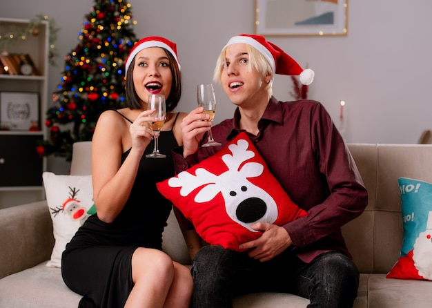 Excité jeune couple à la maison à l'époque de noël portant bonnet de noel assis sur un canapé dans la salle de séjour