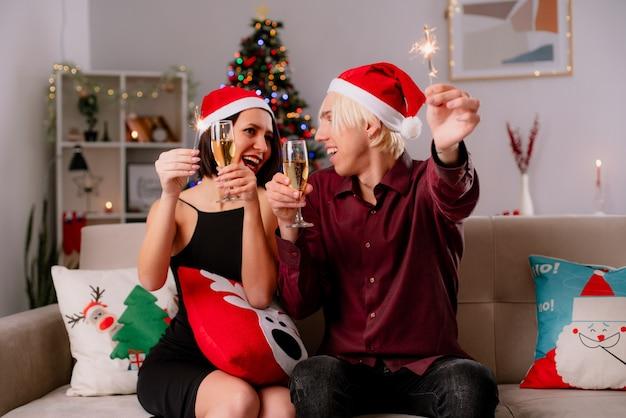 Excité jeune couple à la maison à l'époque de noël portant bonnet de noel assis sur un canapé dans le salon tenant un verre de champagne et de vacances sparkler se regardant avec un oreiller de noël sur ses jambes