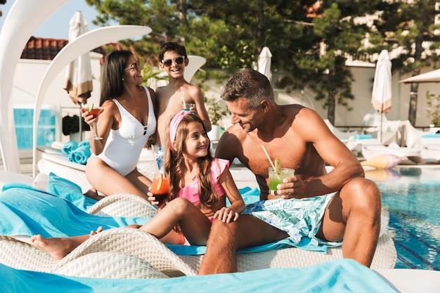 Excité jeune famille s'amusant à la piscine