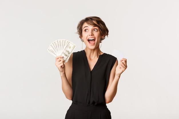 Excité jeune femme accro du shopping hurlant de frisson et tenant une carte de crédit avec de l'argent
