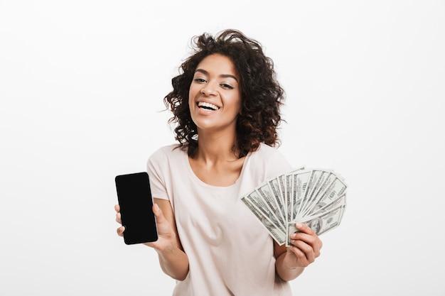 Excité jeune femme américaine avec coiffure afro et grand sourire tenant fan de billets d'un dollar et téléphone portable en argent, isolé sur un mur blanc